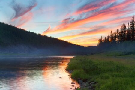 Red clouds over boreal river. The River Amga. Yakutia.