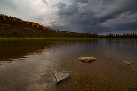 Ominous sky over the taiga river. The River Amga. Yakutia.