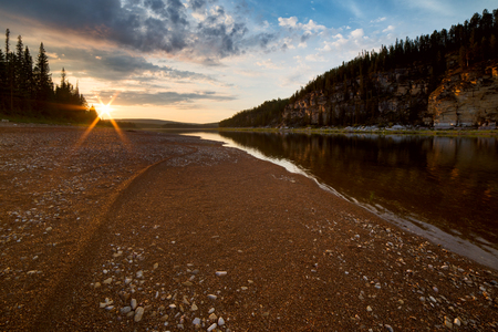 Sunset over boreal river and sandy . The River Amga. Yakutia. Foto de archivo