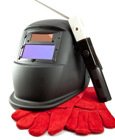 Masque de protection du soudeur, électrode et gants sur fond blanc