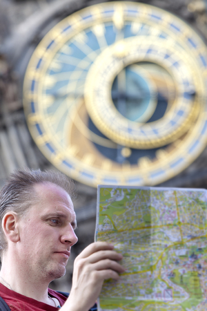 man examines the map on background of historical medieval astronomical Clock on the Old Town Hall in Prague, Czech Republic