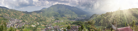 Java, Indonesia. A view from the mountain road on hills with green fields and the village in the valley