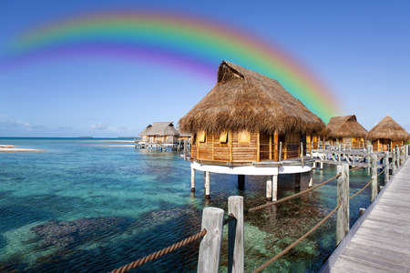 huts over the sea and a rainbow over them