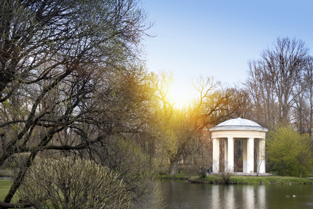 The pavilion on the bank of the lake in the spring park at the beginning of spring, without foliage on trees Stock Photo