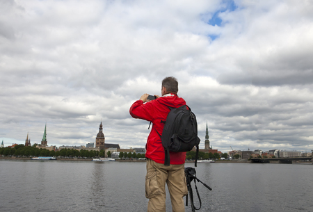 Man, a tourist takes pictures of Riga on the other bank of the Daugava River