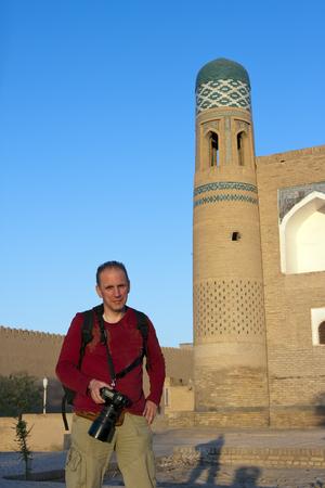 The happy tourist with the camera on the street of  old city Khiva near medieval madrasah. Uzbekistan Stock fotó
