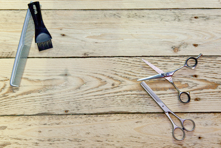 scissors for the hairdresser and comb lie on a wooden board
