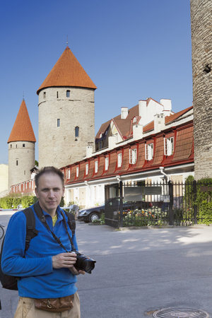 The happy tourist in Tallinn with the camera about medieval towers of a fortification