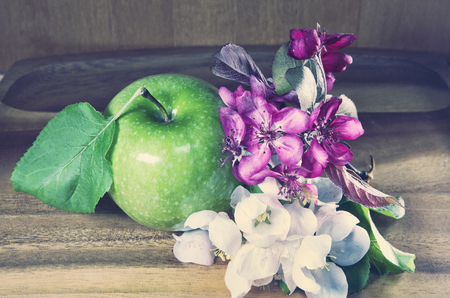 green ripe apple and white and crimson apple tree flowers on wooden background