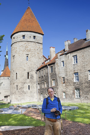 The tourist with the camera on background of medieval towers of a Tallinn fortification