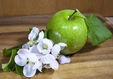green ripe apple and white apple tree flowers on wooden background