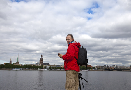 Man, a tourist standing  on the bank of Daugava river against the city of Riga