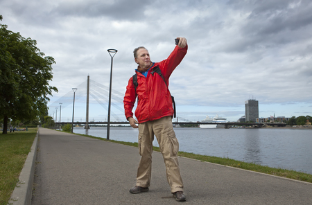 Man, a tourist does selfie, a self-portrait, takes photos of himself on the banks of the Daugava River against the city of Riga