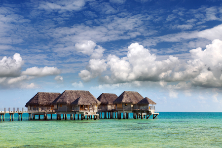 authentic houses with a straw roof over water of the blue sea and the sky with clouds. Polynesia. Stock fotó