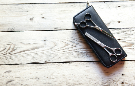 scissors for the hairdresser lie on a wooden board