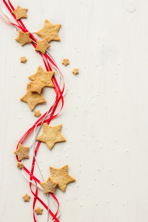 Christmas stars cookies with powder sugar on white wooden background