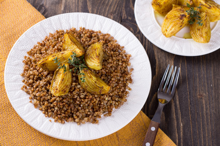 kasha: Buckwheat porridge with baked onions on a wooden table