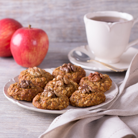 Oatmeal cookies with walnuts, apples and a cup of tea on a wooden surface Archivio Fotografico