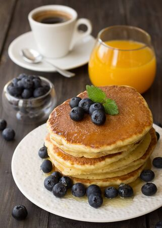 breakfast plate: Pancakes with fresh blueberries and honey on wooden table Stock Photo