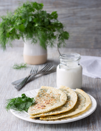 insipid: Flat bread with herbs, kutaby, traditional Azerbaijani dish on a white plate  and on a wooden table