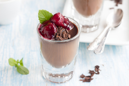 chocolate chips: Chocolate panna cotta with chocolate chips and cherry sauce on a blue background