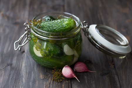 Glass jar of fresh low-salt pickled cucumbers with dill and garlic on a dark wooden table