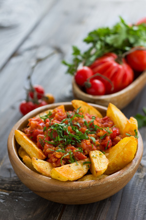 Patatas Bravas, traditional Spanish tapas, baked potatoes with spicy tomato sauce in wooden bowl on wooden table with fresh vegetables. selective focus Archivio Fotografico