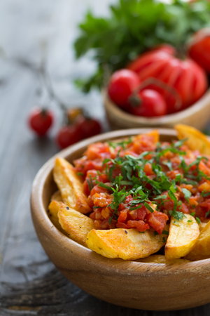 onion: Patatas Bravas, traditional Spanish tapas, baked potatoes with spicy tomato sauce in wooden bowl on wooden table with fresh vegetables. selective focus Foto de archivo