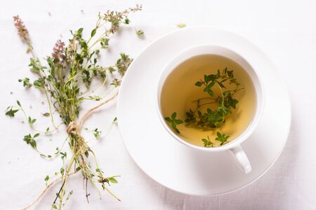 water thyme: Thyme tea in a white cup on a white napkin Stock Photo