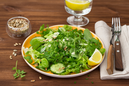 Fresh green salad with various lettuce, cucumber, sunflower seeds and yogurt dressing with honey, olive oil and garlic on wooden table, selective focus