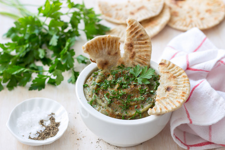 Eggplant dip in a white ceramic bowl with parsley and whole grain flat bread on a light wooden background Stock Photo