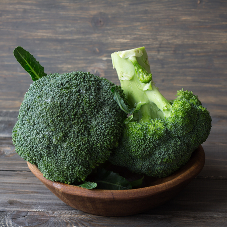 Fresh broccoli in a wooden bowl on wooden table, rustic style