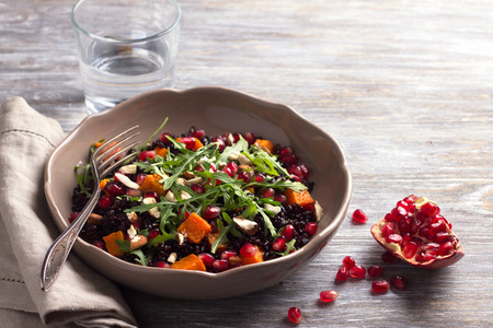 Salad with black rice, baked pumpkin, pomegranate seeds, arugula and nuts on a gray background with free space. Delicious vegan food