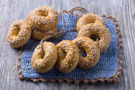 Traditional Greek Easter biscuits Paskhalina Kuluria with sesame seeds on a wooden table. Delicious homemade pastries Stock Photo