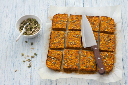 Carrot bars with oatmeal, dried apricots, seeds and honey on a light blue background, selective focus, top view. Healthy energy snack