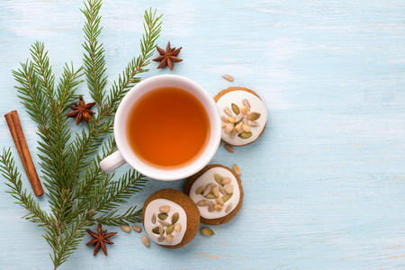 A cup of tea with fragrant honey Christmas gingerbreads with glaze and nuts, with Christmas tree branches and spices on a light blue background, free space, top view 版權商用圖片