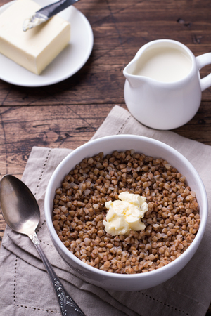 Homemade delicious healthy breakfast. Buckwheat porridge with milk and butter on a wooden table