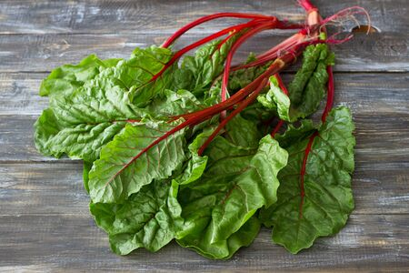 Fresh raw leaves of chard, leaf beets, mangold, swiss chard on a wooden table, close up Stock Photo