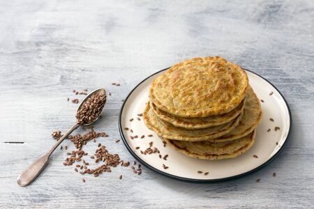 Vegan pancakes with flax seeds on a white plate on a gray background, free space. Delicious homemade healthy food 免版税图像