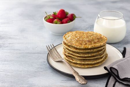Vegan pancakes with flax seeds, strawberry and vegan milk on a white plate on a gray background, free space. Delicious homemade healthy food