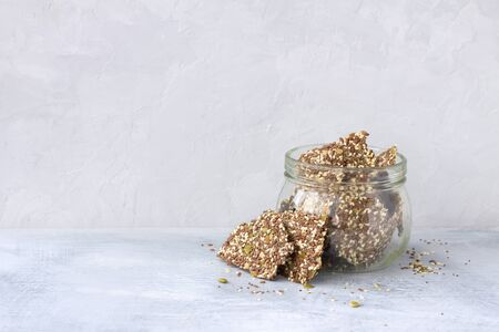 Delicious healthy multigrain gluten-free crackers, ketogenic, from chia seeds, flax, sesame and ground pumpkin seeds in a glass jar on a gray background, free space