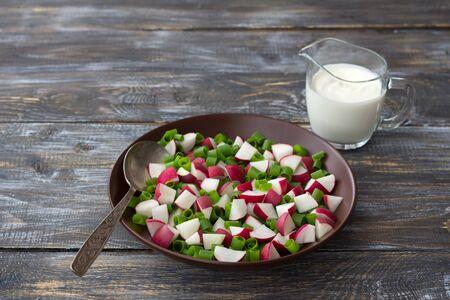 Fresh radish salad with green onions and sour cream on a wooden background, rustic style. Delicious homemade food