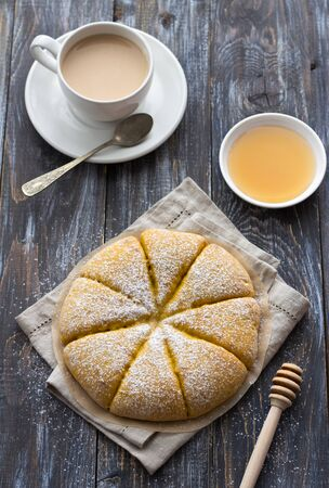 Freshly baked carrot scones with honey and cup of tea with milk on wooden background. delicious homemade cakes