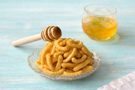 Chak chak, stukjes deeg in honing, tatar traditioneel dessert op lichtblauwe achtergrond