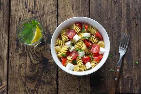 Homemade salad with pasta, tomatoes, feta cheese and spices on wooden table. simple delicious food. top view, space