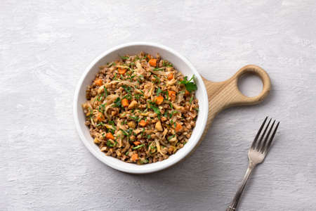 Delicious vegetarian buckwheat with cabbage, carrots, onions, nuts and herbs on a light gray textured background, top view. Homemade diet healthy food Archivio Fotografico