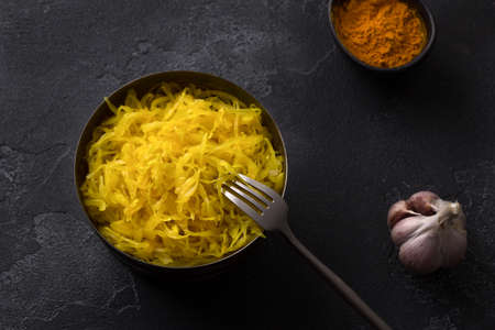 Homemade sauerkraut with garlic, onion and turmeric on a dark textured background. healthy fermented food, natural probiotic, vegan food. top view