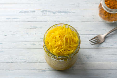 Homemade sauerkraut with garlic, onion and turmeric on a light blue background. healthy fermented food, natural probiotic, vegan food. top view, space Archivio Fotografico