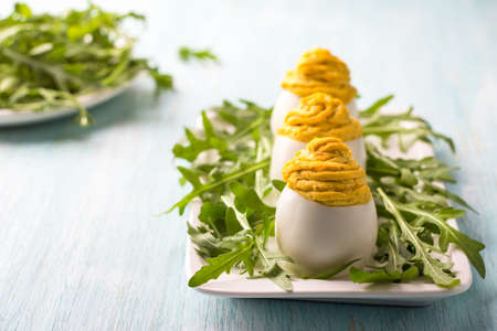 Boiled eggs stuffed with fried onions and turmeric with fresh arugula on light blue background. delicious homemade snack