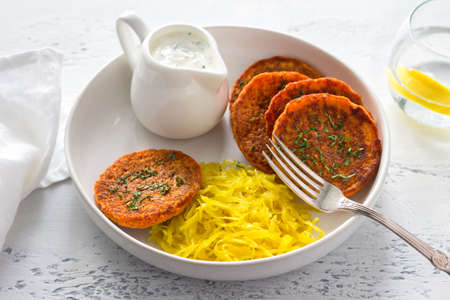 Lentil fritters with turmeric sauerkraut and yogurt sauce with greens in a white plate on a light blue textured background. Healthy vegan food